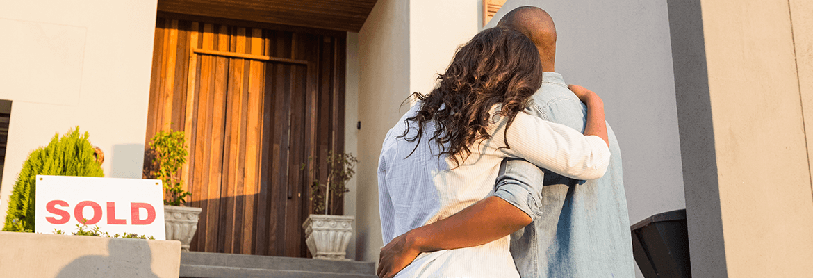 A Couple Embracing After Buying A House