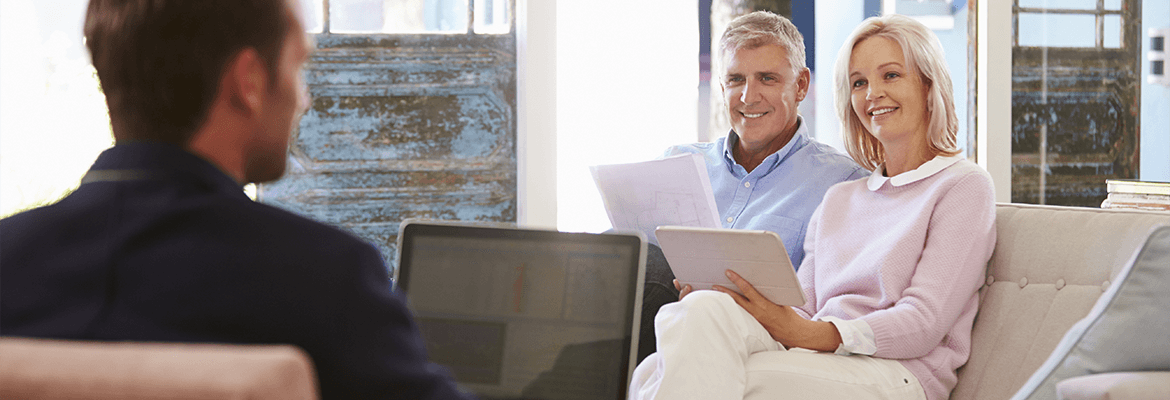 Mature Couple Sitting At Home With A Financial Advisor